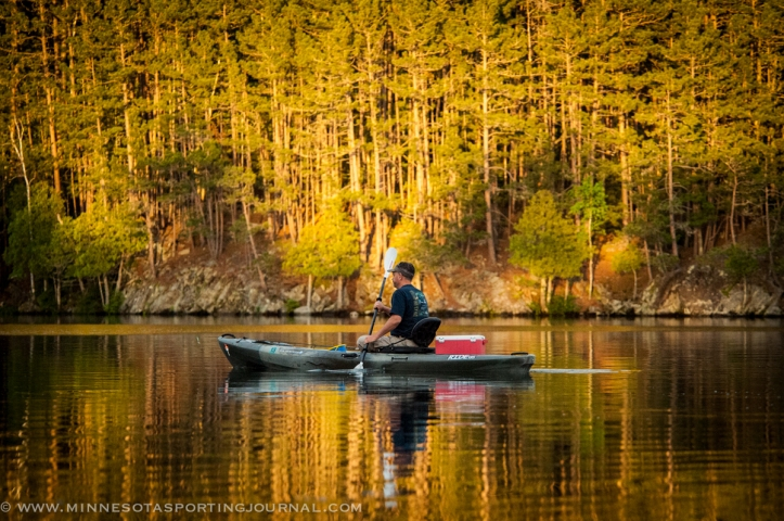 Jim Riley paddles through the sun-splashed reflection of the trees.
