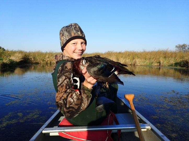 "Dave Jungst submitted this photo and added: ""Another warm day. Hardly seems like duck opener weather, but it was a beautiful day to float hunt the river and my mentee, Bennett did a great job with his 20 gage and bagged a limit of Wood ducks."""