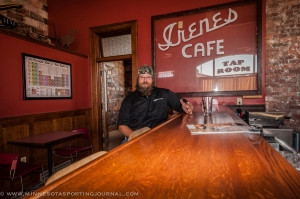 Jason Markkula sits at the bar in his tap room, which once housed a bank and a cafe which is memorialized on the wall.