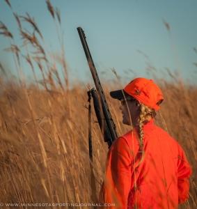 Mandy Uhrich walks the tall grass of a State Wildlife Management Area near Worthington, MN