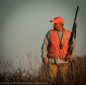 "Chris Kruse watches his dog ""Gator"" work some tall grass near Worthington, MN"