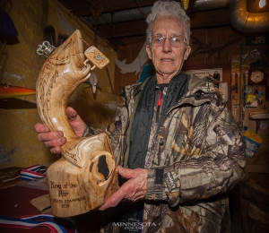 Mary Lou Schneider with a trophy that she carved.