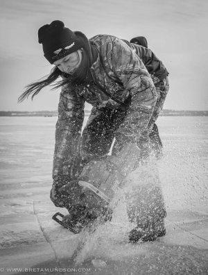 Trisha Steffen uses a chainsaw to cut into Lake Winnebag prior to the Sturgeon Spectacular. (Bret Amundson/Sporting Journal Radio)